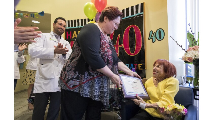 Edda Spinelli, regional director of operations for Avantus Renal Therapy in Newport Beach, presents Celia Kanter, 77, with a certificate of recognition Friday for achieving the milestone of 40 years on dialysis.
