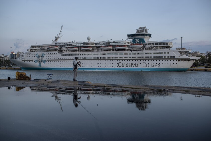 A man fishes in front of a docked cruise ship in Piraeus port, near Athens, Greece, Wednesday, May 27, 2020. About 150,000 seafarers are stranded at sea in need of crew changes, according to the International Chamber of Shipping. Roughly another 150,000 are stuck on shore, waiting to get back to work. (AP Photo/Petros Giannakouris)