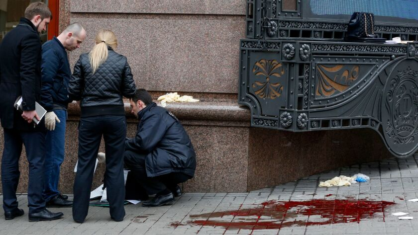 Forensics experts and police officers examine the scene where Denis Voronenkov was killed in Kiev, Ukraine, on March 23.