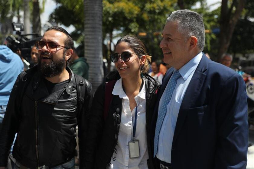 Two reporters from Spanish international news agency EFE who were detained overnight in Caracas, Mauren Barriga (center) and Leonardo Muñoz (left), are accompanied by the charge d'affaires of Colombia's embassy in Venezuela, German Castañeda, after being released on Jan. 31, 2019. EPA-EFE/Miguel Gutierrez