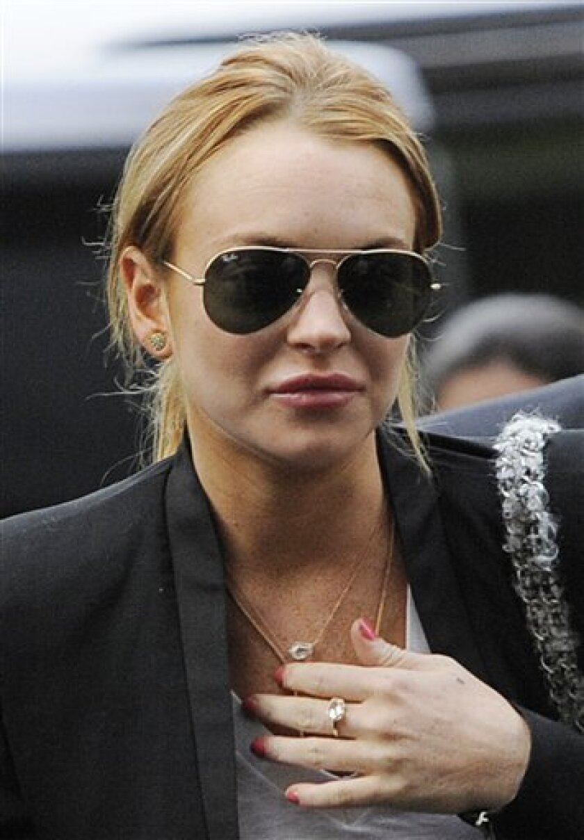 FILE - In this Oct. 22, 2010 file photo, Lindsay Lohan arrives for a probation violation hearing at Beverly Hills Courthouse in Beverly Hills, Calif. Sheriff's investigators in California want Lindsay Lohan charged with battery for last month's skirmish with a Betty Ford Center rehabilitation technician, The Associated Press reports Tuesday, Jan. 4, 2010. A riverside sheriff's sergeant says a two-week investigation shows Lohan violated her probation during the Dec. 12 altercation. Results will be sent to the probation department and prosecutors. Lohan was scheduled to get out of rehab on Monday, but it's not clear she's still there. (AP Photo/Chris Pizzello, File)