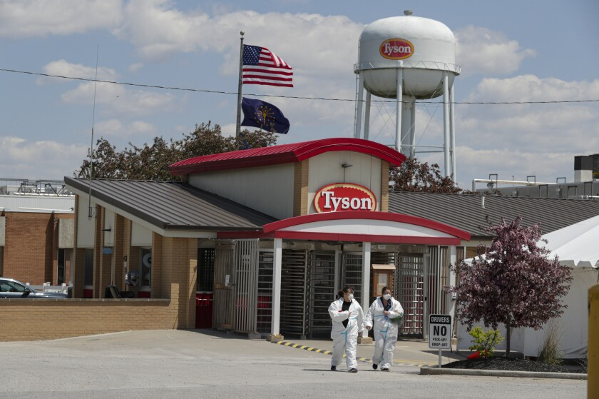 FILE - In this May 7, 2020 file photo, workers leave the Tyson Foods pork processing plant in Logansport, Ind. Tyson Foods, on Friday, Sept. 3, 2021 is offering paid sick leave for the first time to its front-line workers, part of an agreement that secured union support for its mandate that all U.S. employees get vaccinated against the COVID-19 virus. (AP Photo/Michael Conroy, File)
