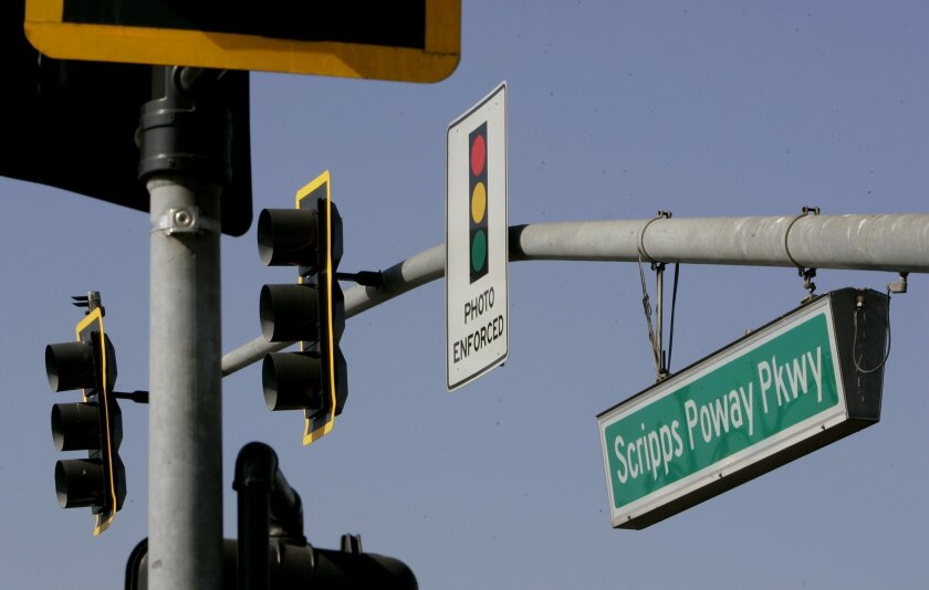 A sign warns motorists of red-light cameras on northbound Community Road at Scripps Poway Parkway.