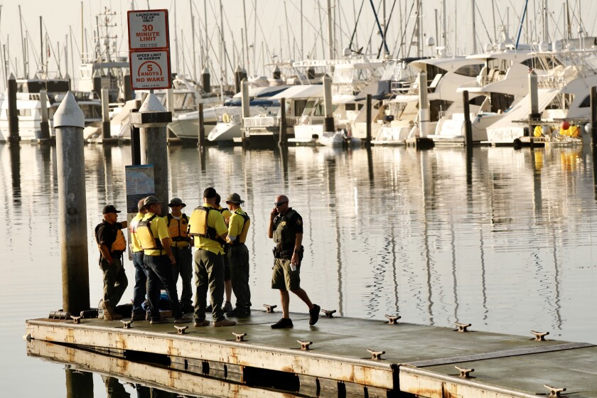 Law enforcement officials at Santa Barbara Harbor wait for a boat to take them to the scene of the deadly boat fire off Santa Cruz Island.