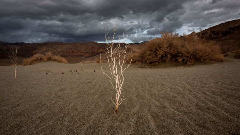 A storm approaches desert sands near Lone Pine, Calif. California agriculture faces a future of drought and flooding.