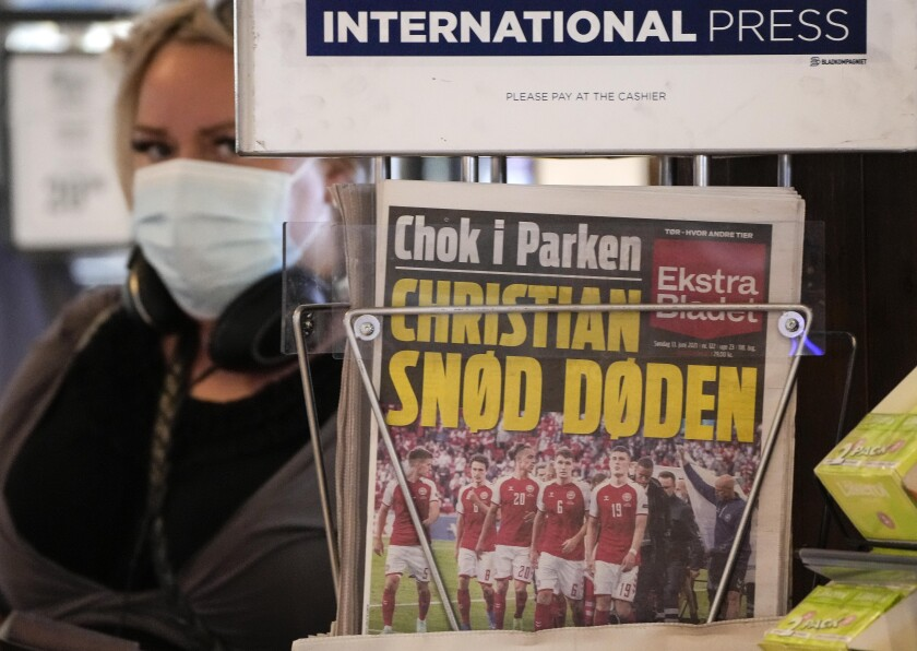 A front-page of a newspaper shows the shocked Danish soccer team escorting player Christian Eriksen, at a newsstand at the central station in Copenhagen, Denmark, Sunday, June 13, 2021. Eriksen collapsed on the pitch during the European Championship game against Finland yesterday and needed CPR from medical staff before regaining consciousness. (AP Photo/Martin Meissner)