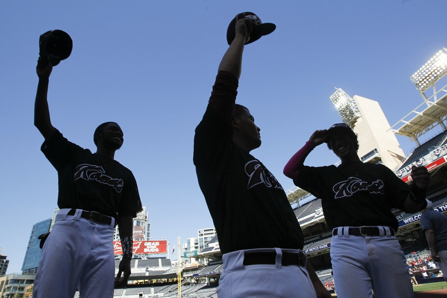 Kearny's Travis Gooden, left, Dan Agulto, center, and Smitt Thirakul have fun seeing what it's like to step out of the dugout and tip their caps like the pros before they play Hoover at Petco Park on Friday. 4/17/15