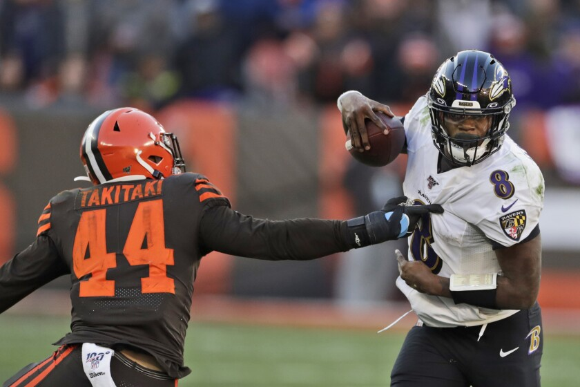 Baltimore Ravens quarterback Lamar Jackson avoids a tackle by Cleveland Browns linebacker Sione Takitaki during the second half on Sunday in Cleveland.