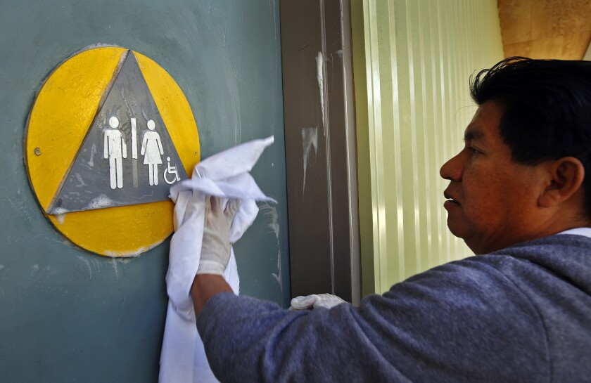 A maintenance worker cleans the front doors of a restroom with a gender-neutral sign in West Hollywood in January. A ballot initiative that sought to require transgender people to use the public restrooms that correspond with their biological sex has failed to qualify for the California ballot, backers say.