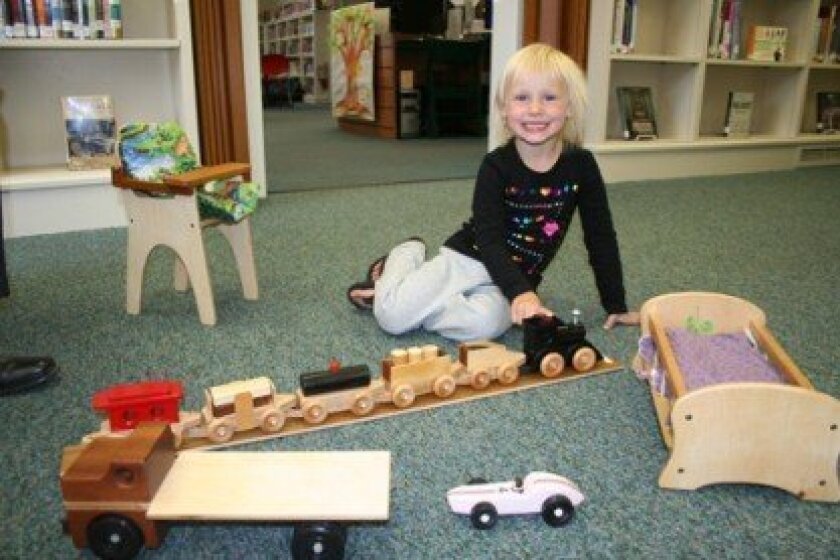 Cassidy Lyle plays with the new toys from the San Diego Fine Woodworkers Association at the Rancho Santa Fe Library. –Photo/Karen Billing