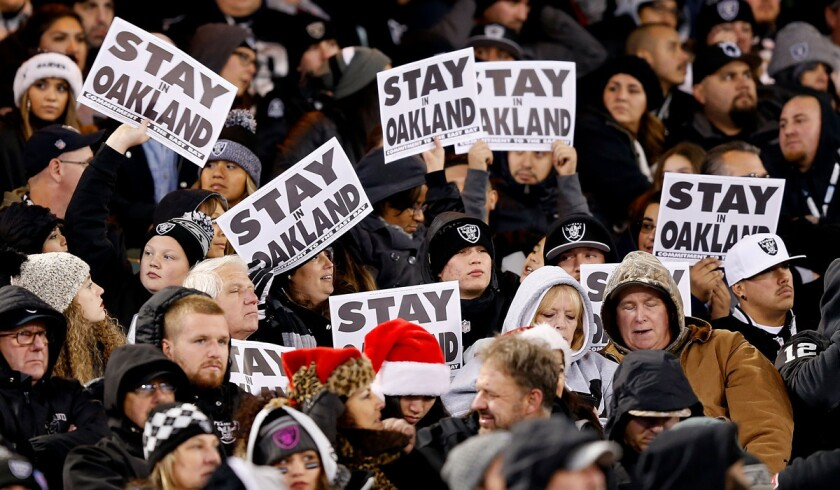 """Oakland Raiders fans show """"Stay In Oakland"""" signs during the game against the San Diego Chargers on Dec. 24."""