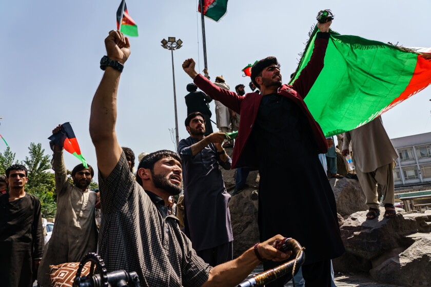 Afghans try to raise the national flag of Afghanistan at Pashtunistan Square in Kabul