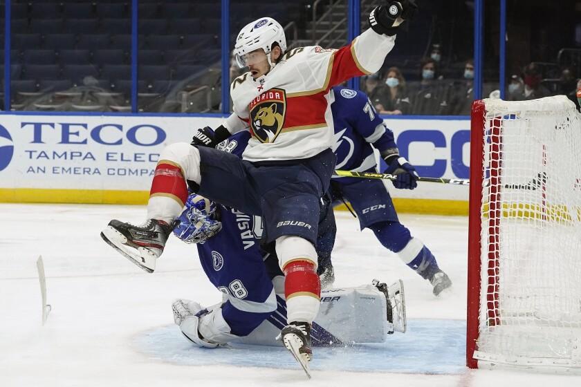 Florida Panthers defenseman MacKenzie Weegar (52) falls on Tampa Bay Lightning goaltender Andrei Vasilevskiy (88) after a shot during the third period of an NHL hockey game Thursday, April 15, 2021, in Tampa, Fla. (AP Photo/Chris O'Meara)