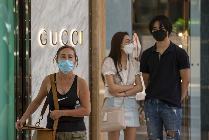 Shoppers wear masks as they wait in line outside at South Coast Plaza  in Costa Mesa.