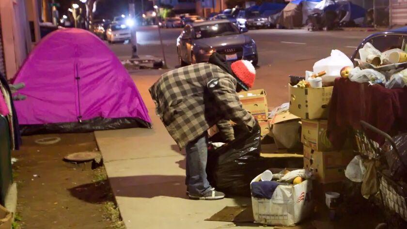 Homeless men and women congregate on 17th Street in downtown San Diego's East Village neighborhood on Jan. 27, 2017.