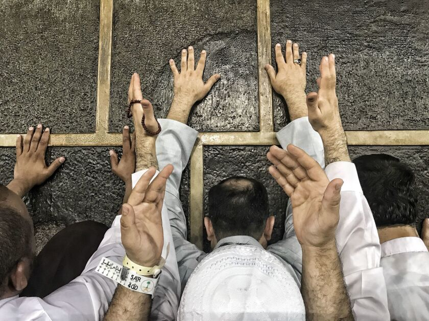 Hajj pilgrims touch the wall of the Kaaba, Islam's holiest site, in the Saudi Arabian city of Mecca on Saturday. About 2 1/2 million Muslims are expected to take part in the pilgrimage to Mecca this year.