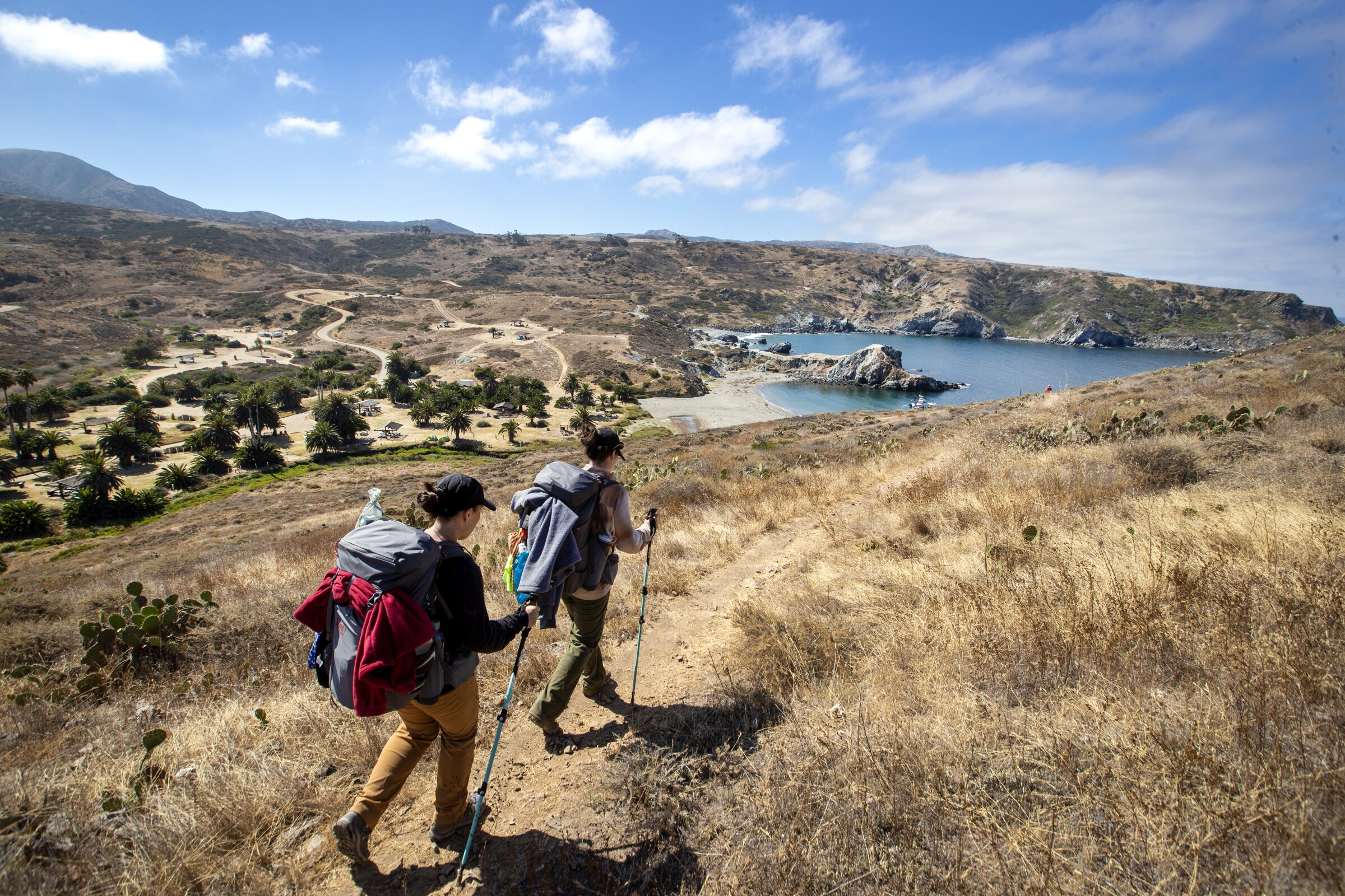 Two hikers, wearing backpacks, arrive at Little Harbor campground.