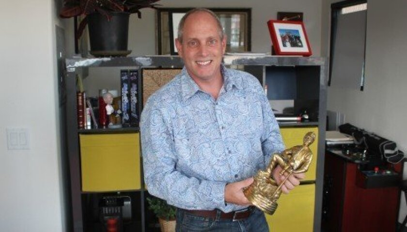 La Jolla author Greg S. Reid poses with a gold miner statue he received as an award.. Reid is co-author of several books, including 'Three Feet from Gold: Turn Your Obstacles in Opportunities.' Pat Sherman