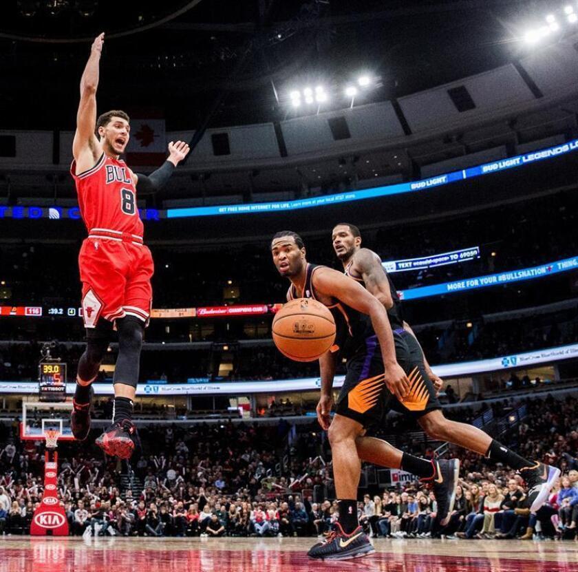 El escolta Zach LaVine (i) de Chicago Bulls pierde la bola ante la marca de los aleros Trevor Ariza (d) y TJ Warren (c) de Phoenix Suns hoy, durante un partido entre Phoenix Suns y Chicago Bulls de la NBA, en el United Center en Chicago, Illinois (Estados Unidos). EFE