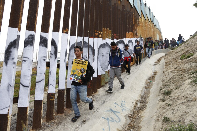 Supporters and migrants walk along the fence.