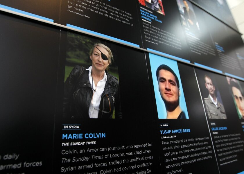 FILE- In this May 13, 2013, file photo, the photo of Journalist Marie Colvin who was killed in Syria while she was reporting from there, is seen on the wall of the Newseum during the Journalist Memorial Re-dedication ceremony of the journalists who died reporting the news in 2012 in Washington. Relatives of Colvin, a U.S.-born journalist who worked for the British newspaper The Sunday Times, have filed a lawsuit in federal court in Washington claiming that Syrian government officials targeted her and killed her four years ago to silence her reporting on Syria and the besieged city of Homs. (AP Photo/Jose Luis Magana, File)