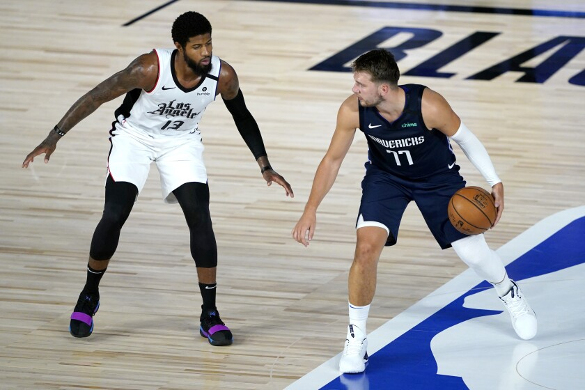 Dallas Mavericks forward Luka Doncic tries to work past Clippers forward Paul George during a game on Aug. 6.