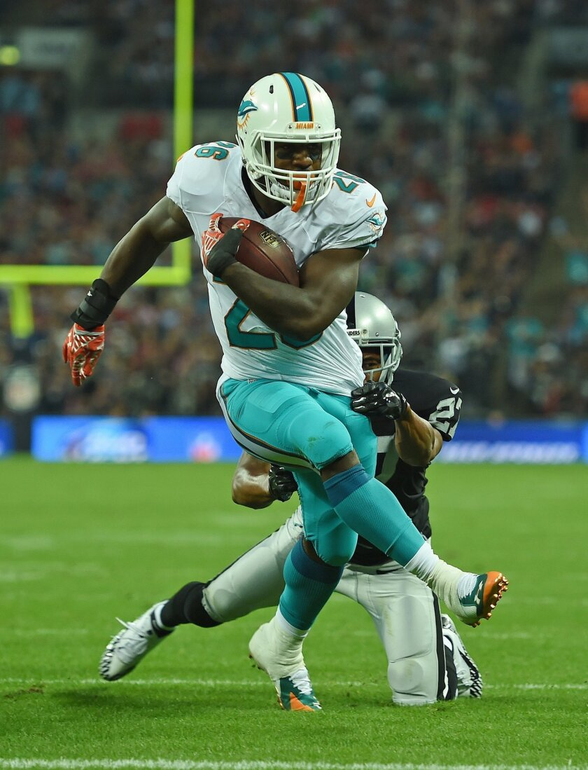 Miami Dolphins' Lamar Miller breaks a tackle on his way to scoring a touchdown during the NFL football game against Oakland Raiders at Wembley Stadium in London, Sunday, Sept. 28, 2014. (AP Photo/Tim Ireland)