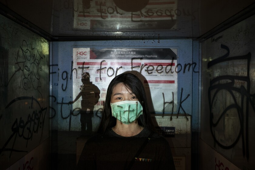 """In this Oct. 19, 2019, photo, a 24-year-old protester who identified herself as Josephine, poses for a portrait as a projector displays a photograph, previously taken during the unrest, over her at a protest in Hong Kong. Josephine said she is afraid of the mask law, """"but we are still coming out because we need to find hope, to find the future of Hong Kong."""" (AP Photo/Felipe Dana)"""