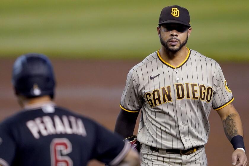 Padres' Tommy Pham looks towards Arizona Diamondbacks' David Peralta (6) as he leaves game in August.