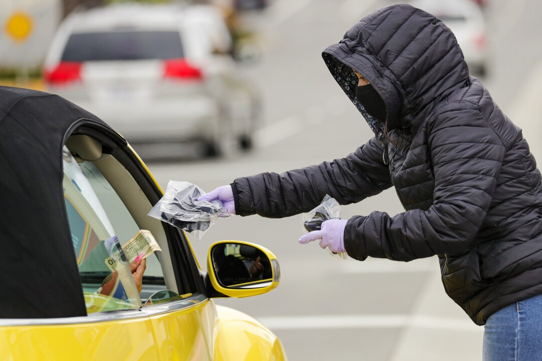 Stephanie Reyes, 16, sells masks to a traveler on the 3000 block of West Century Boulevard in Inglewood.