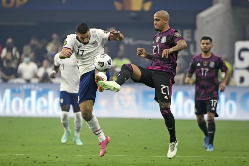 U.S. midfielder Sebastian Lletget and Mexico defender Luis Rodriguez battle for the ball.