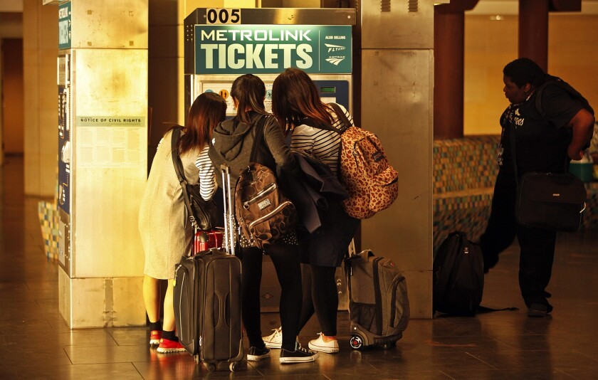 A group of Metrolink passengers crowd around a ticket vending machine at Patsaouras Transit Plaza in Union Station. According to rail officials, riders and complaints on social media, the devices have been breaking down with irritating frequency.