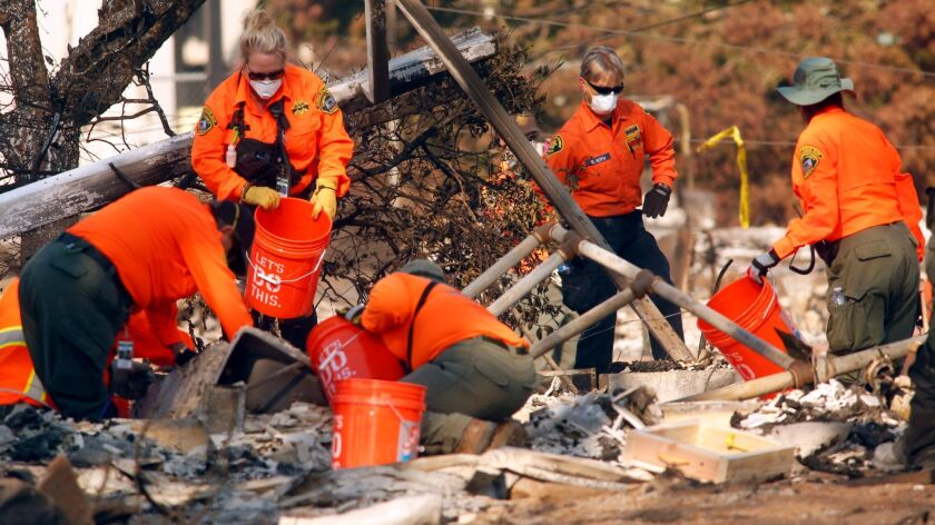Search-and-rescue workers sift through the debris of a fire-ravaged home in Santa Rosa, Calif., on Oct. 15.