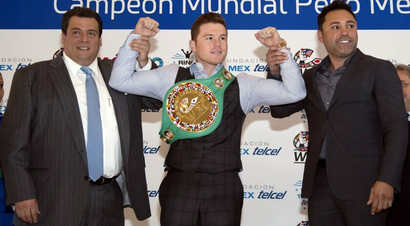 Mauricio Sulaimán (i) presidente del CMB, 'Canelo' Álvarez con el cinturón diamante (c) y Óscar de la Hoya.
