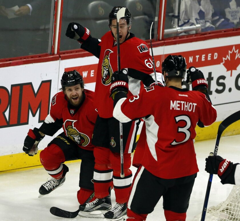 Ottawa Senators' Zack Smith (15) celebrates his goal with teammates Marc Methot (3) and Mark Stone (61) during the first period of an NHL hockey game against the Toronto Maple Leafs in Ottawa, Ontario, on Saturday, Feb. 6, 2016. (Fred Chartrand/The Canadian Press via AP)