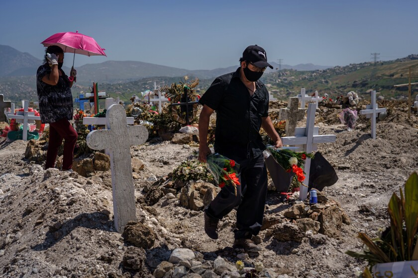 A relative arrives with flowers for the burial of Juan Velasco at a cemetery in Tijuana on April 27, 2020.
