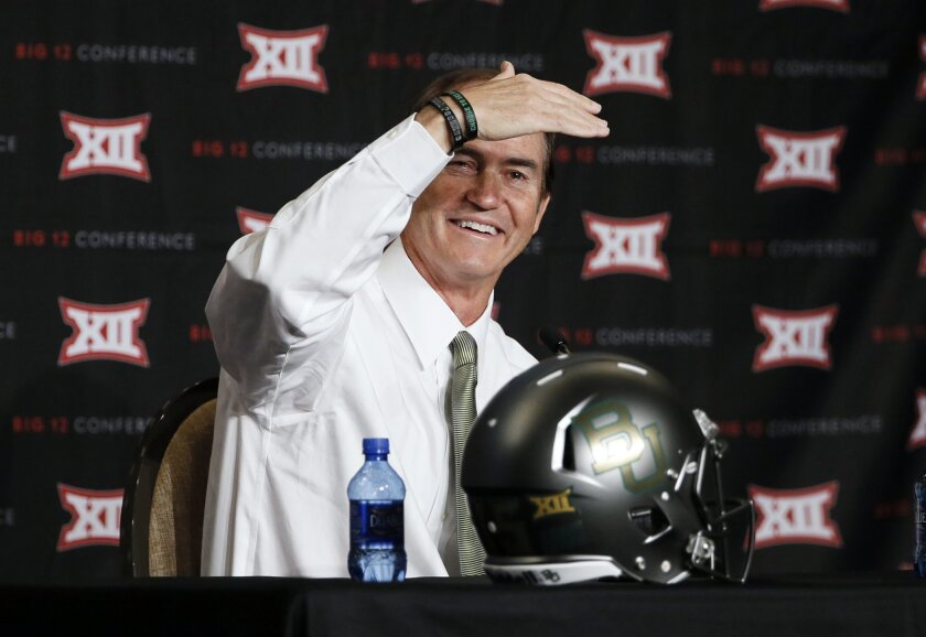 FILE - In this July 21, 2015, file photo, Baylor head coach Art Briles shields his eyes from the lights as he addresses attendees at the Big 12 Conference Football Media Days in Dallas. The quarterback is usually the face of a football team. During conference media days, those faces are often difficult to find. (AP Photo/Tony Gutierrez, File)