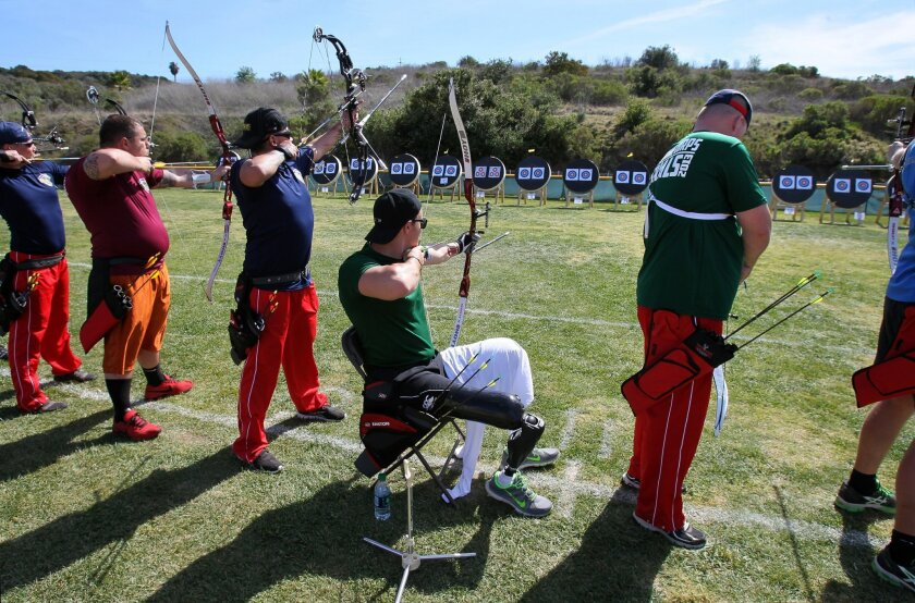At the Marine Corps Warrior Game Trials last year at Camp Pendleton's Lake O'Neill Recreation Park, Curtis McGrath, a former combat engineer from the Australian Army, prepares to shoot an arrow during the archery competition. Watching at far left and giving advice is archery instructor Darryl Wood,