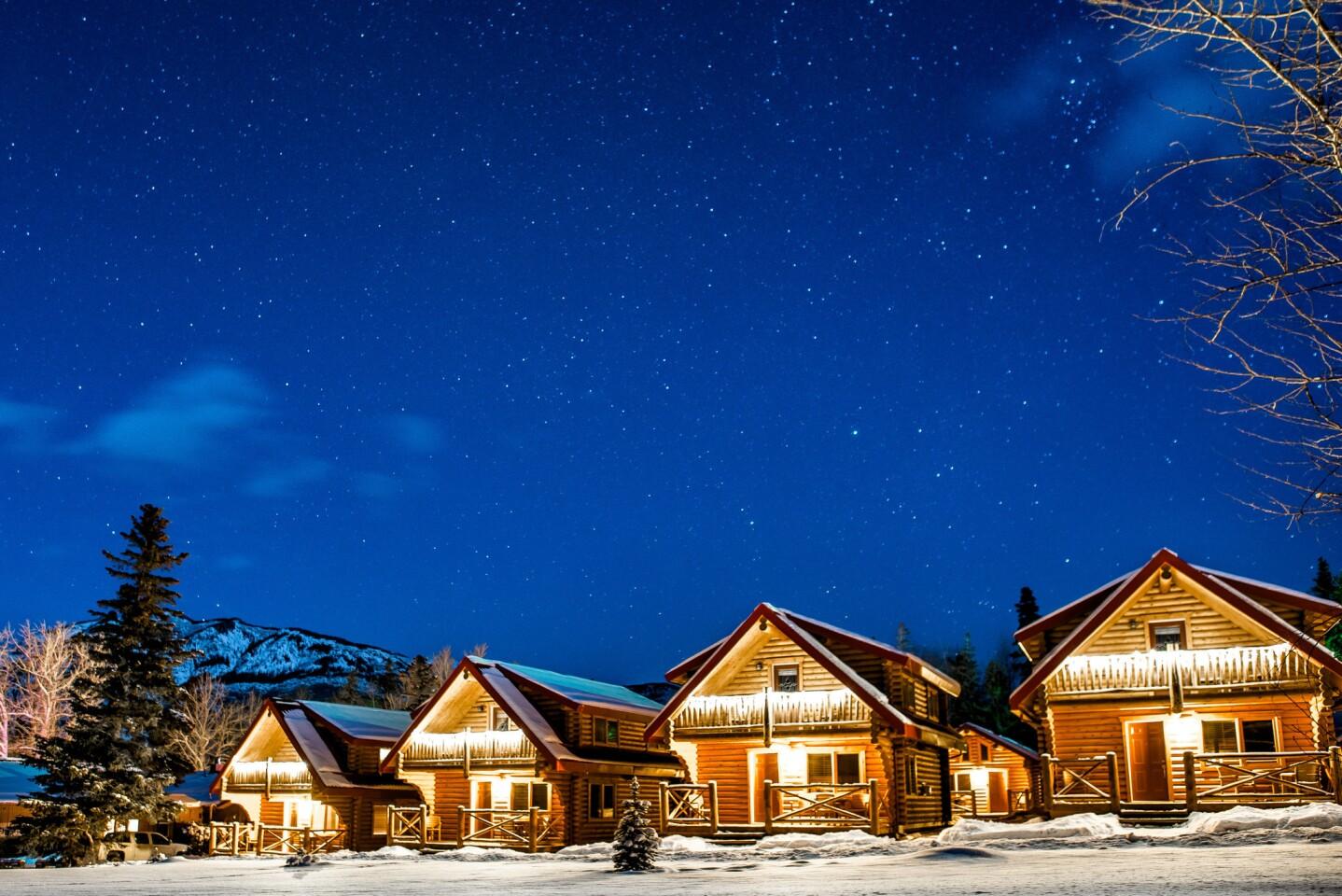 Cabins glow in the night in Jasper, Canada.