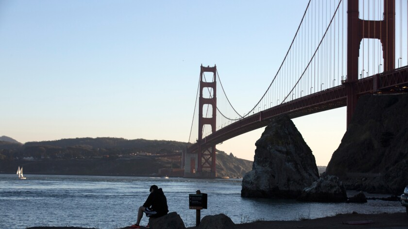 A man sits on a rock overlooking the Golden Gate Bridge on Nov. 11, 2015.