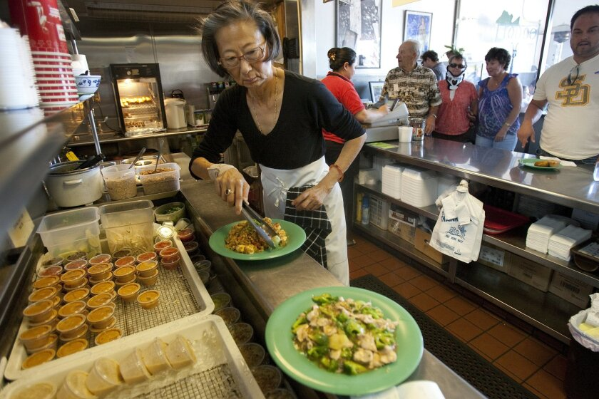 Su-Mei Yu, owner of Saffron, checks on orders before they are delivered to customers during the lunch rush.