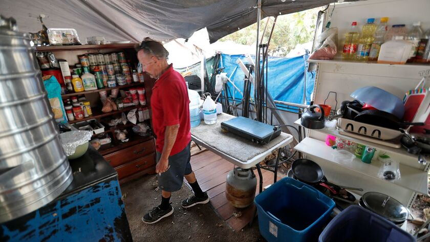 Scott West, 55, who has been homeless for five years, opens his pantry inside his tent compound alon