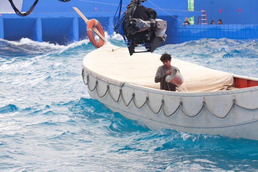 """Actor Suraj Sharma alone on a lifeboat in a water tank against a blue screen in scene from """"Life of Pi,"""" for which Rhythm & Hues received an Academy Award."""