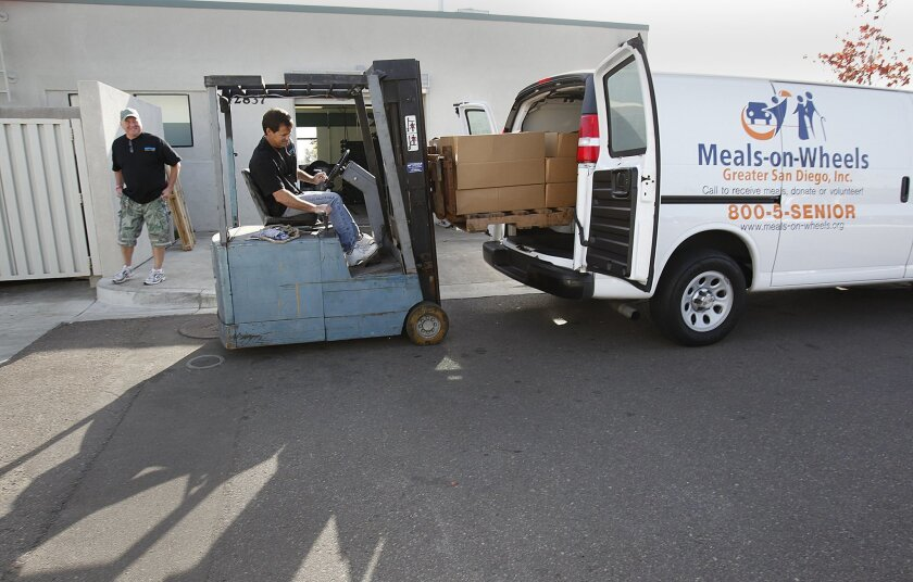 Sean Sebring, owner and manager of Fishermen's Processing in Liberty Station, loads boxes of fish into a van for Meals-on-Wheels Greater San Diego. A local nonprofit group called Fish. Food. Feel Good. collects donated fish from the docks and gives it to charities that feed poor and elderly residen