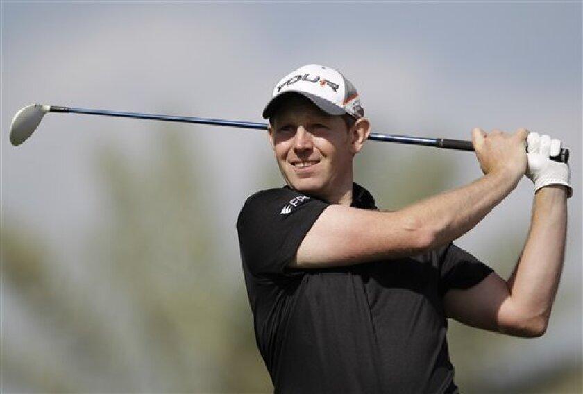 Stephen Gallacher of Scotland tees off on the 9th hole during final round of the Dubai Desert Classic Golf tournament in Dubai, United Arab Emirates, Sunday, Feb. 3, 2013. (AP Photo/Kamran Jebreili)