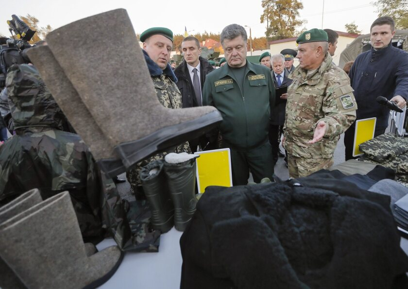 Ukrainian President Petro Poroshenko, center, inspects winter gear and ammunition for a border guard unit near Kiev on Tuesday. A Sept. 5 cease-fire has all but collapsed as fighting intensifies over strategic venues in eastern Ukraine.