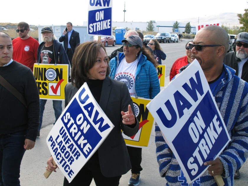 Sen. Kamala Harris, D-Calif., talks to a union leader while she walks a picket line with striking UAW members, Thursday, Oct. 3, 2019 at a General Motors facility just north of Reno, Nev.. The Democratic presidential hopeful said she wanted to stand in solidarity with unions who are responsible for creating a middle class that's under siege under the Trump administration. (AP Photo/Scott Sonner)
