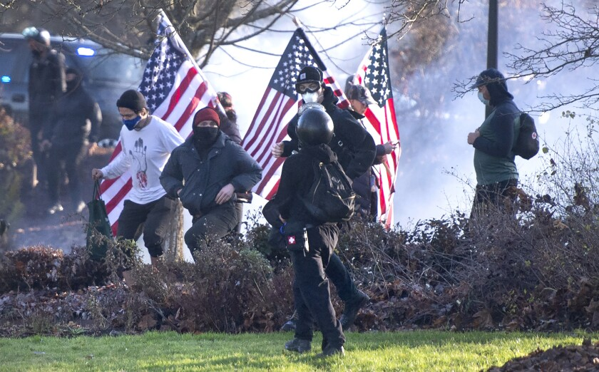 Supporters of President Donald Trump and antifa supporters clashed with Washington state police on the state Capitol Campus in Olympia, Wash., Saturday, Dec. 12, 2020. Police in Olympia declared a riot early Saturday afternoon and arrested at least one person as groups with different points of view held simultaneous protests. (The Olympian via AP)