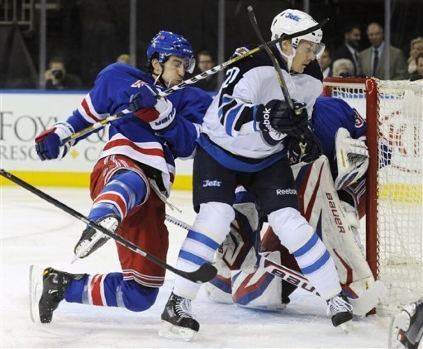 New York Rangers' Michael Del Zotto, right, loses his balance as he is checked by Winnipeg Jets' Antti Miettinen during the first period of an NHL hockey game Monday, April 1, 2013, at Madison Square Garden in New York.  (AP Photo/Bill Kostroun)