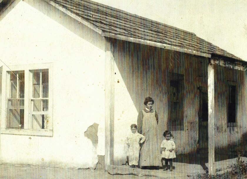 Image of a one-story house with a woman and two children standing out front.